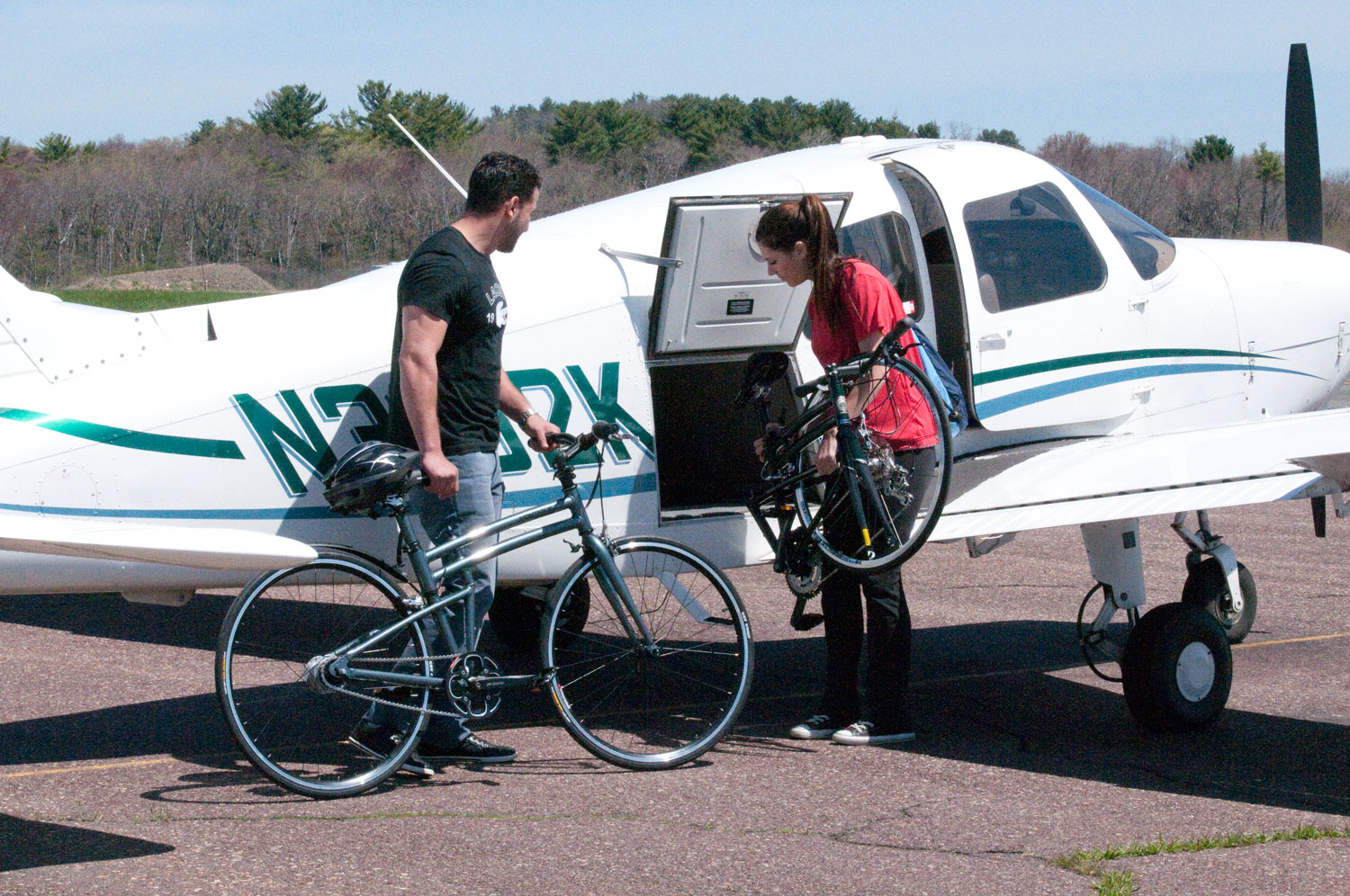 Man and Woman with Folding Bikes and Private Plane